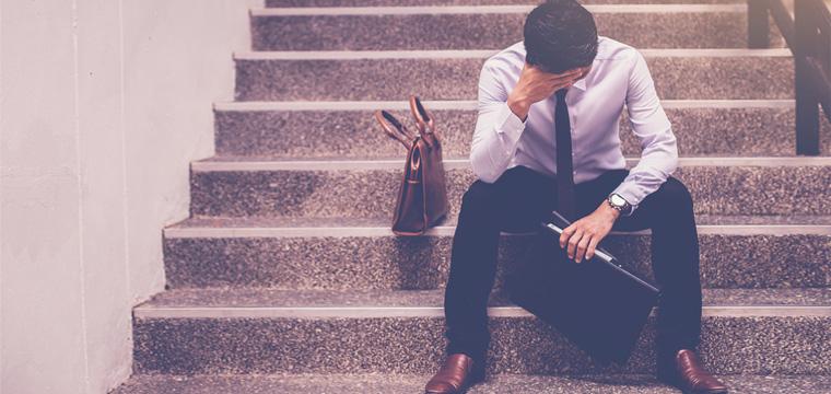 Junger Mann sitzt verzweifelt auf einer Treppe.