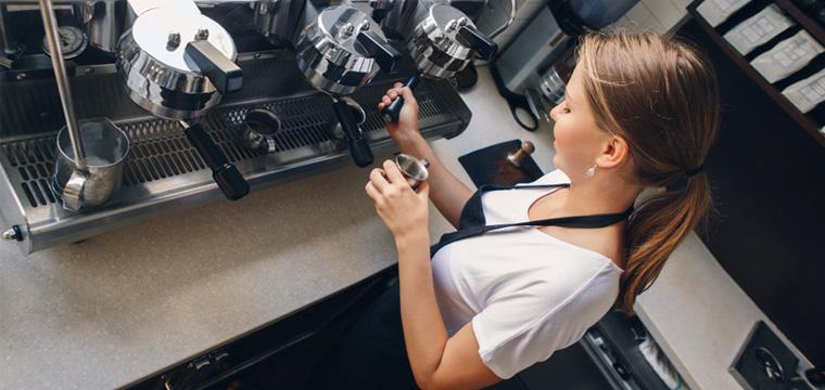 Eine junge Frau bedient eine Siebträger-Kaffeemaschine.