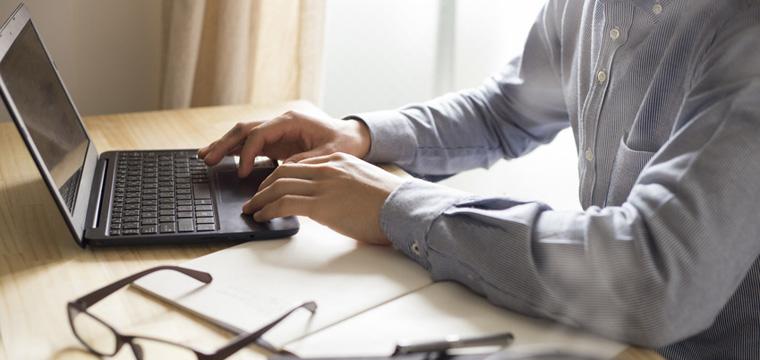 Hände eines jungen Studenten arbeiten an Laptop.