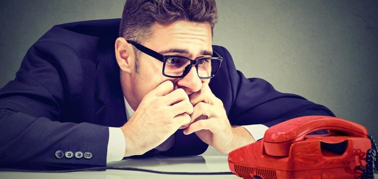 Junger Mann in Business Outfit wartet verzweifelt vor einem Telefon.