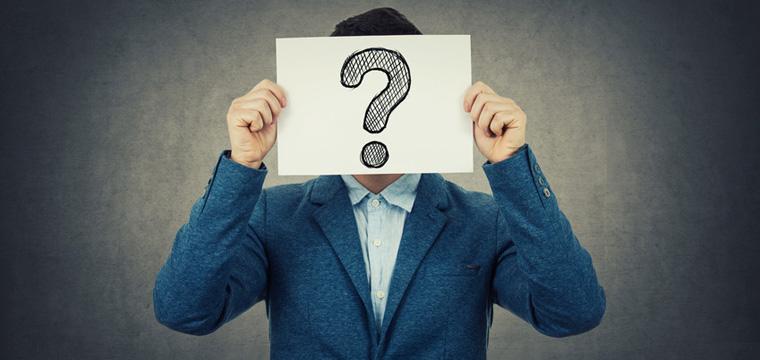 Mann hält Blatt Papier mit großem Fragezeichen vor sein Gesicht.