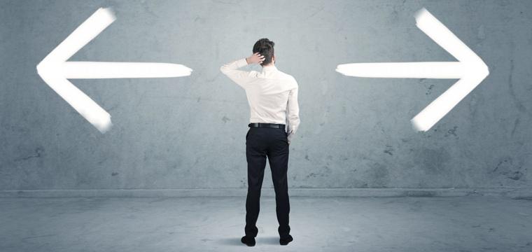 Junger Mann steht vor Wand mit Pfeilen nach rechts und nach links und fasst sich an den Kopf.