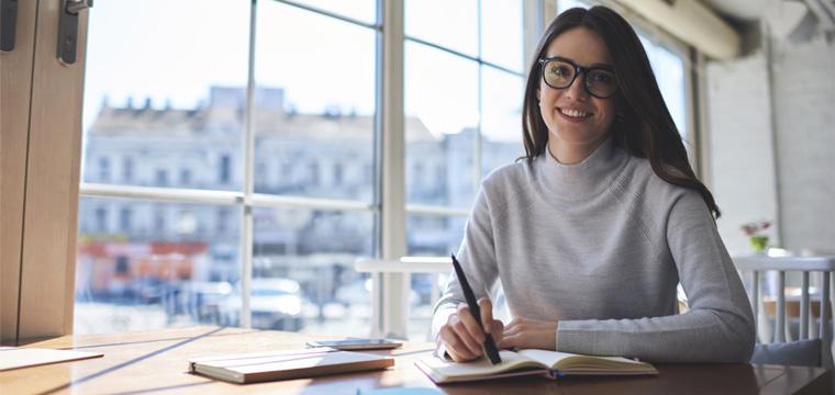 Eine junge Frau sitzt an einem Tisch und lächelt in die Kamera.