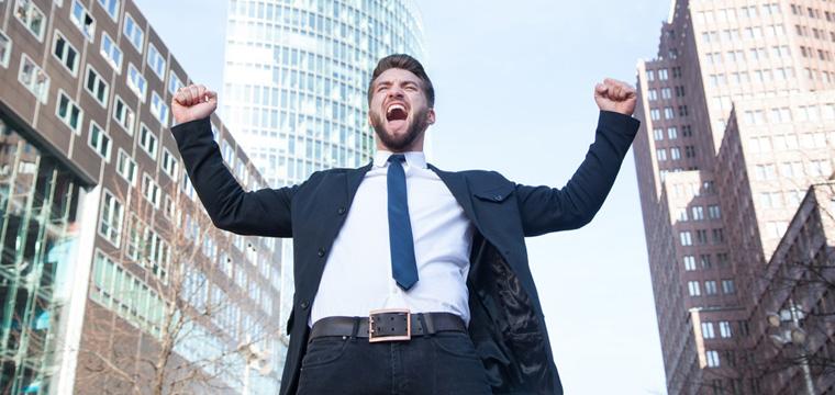Ein junger Mann jubelt nach erfolgreicher Initiativbewerbung.