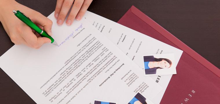 Junge Frau unterschreibt das Anschreiben ihrer Bewerbung.