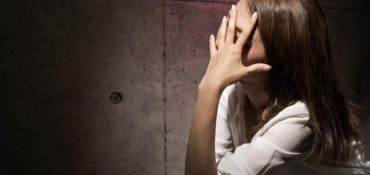Eine Frau sitzt geschockt auf dem Boden, die Hand vorm Gesicht.