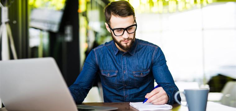 Junger Mann sitzt vor Laptop und prüft handschriftliche Notizen.