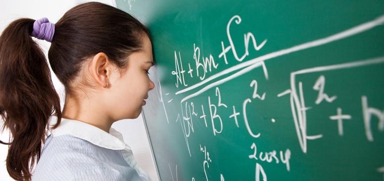 Erschöpfte Studentin lehnt den Kopf gegen die Tafel.