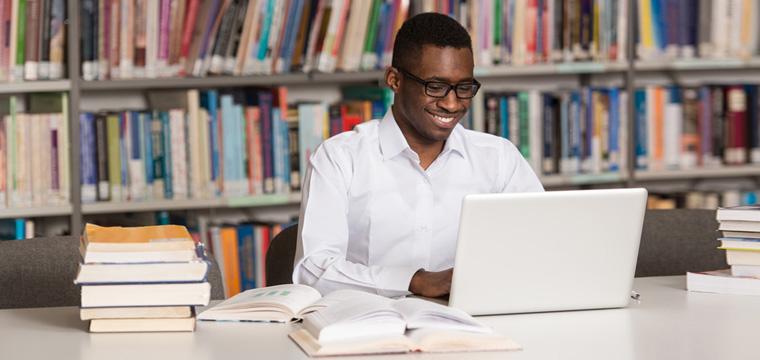 Ein Student sitzt zwischen Bücherstapeln lächelnd vor seinem Laptop.