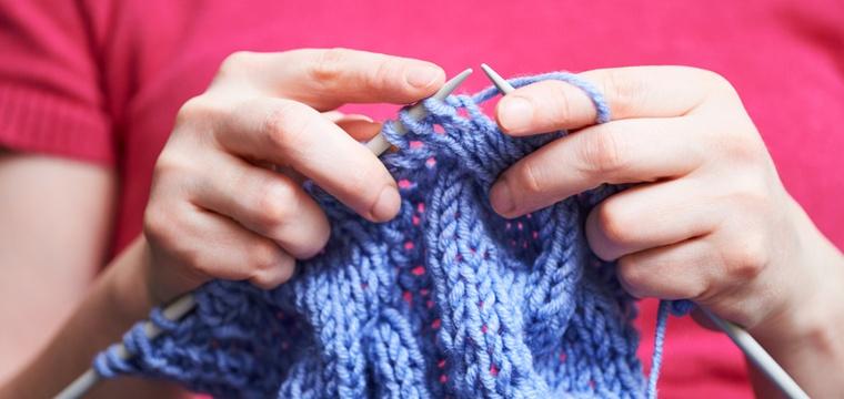 Frauenhände, die einen Schal stricken, in Nahaufnahme.