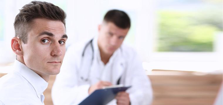 Mann sitzt vor Arzt