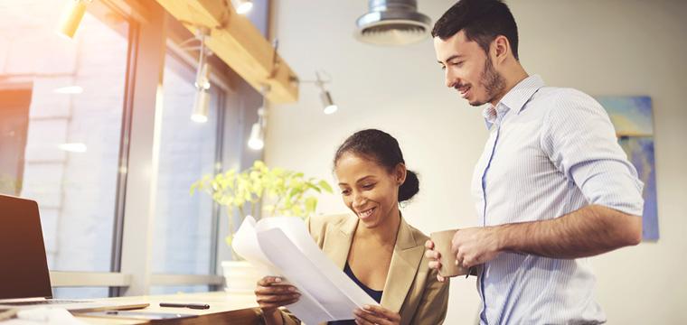 Lächelnde junge Managerin bekommt eine Kurzbewerbung gezeigt.