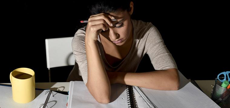Junge Frau sitzt verzweifelt vor ihren Uni-Unterlagen.