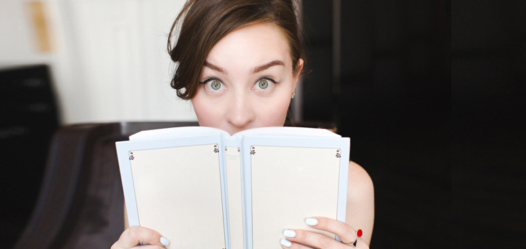 Junge Frau schaut hinter Buch hervor