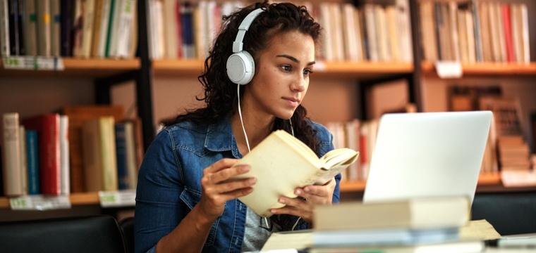 Studentin vor Laptop in Bibliothek