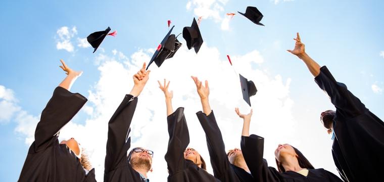 Absolventen werfen Doktorhüte
