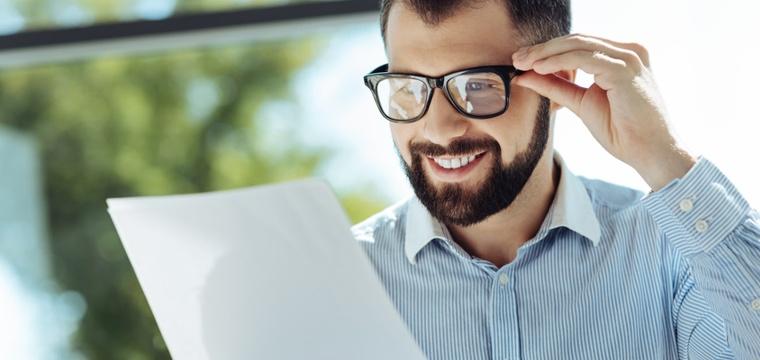Junger Mann mit Bart schaut sich lächelnd ein Referenzschreiben an.