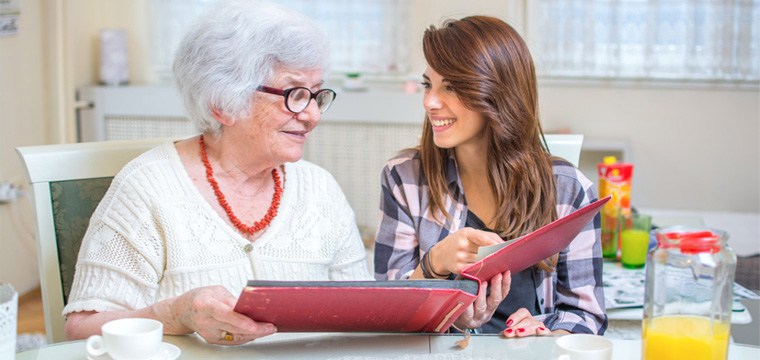 Eine Seniorin sitzt mit einer jüngeren Frau am Tisch.