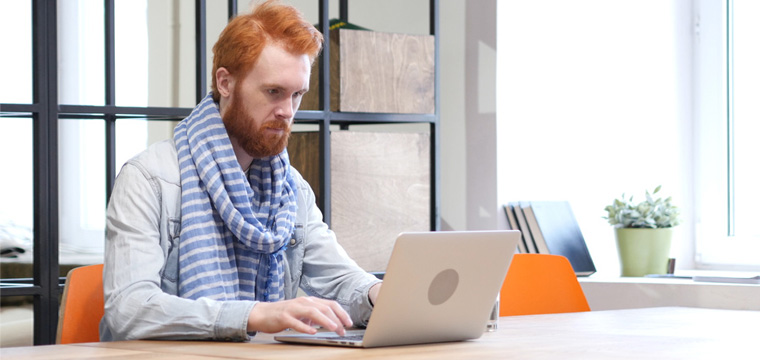 Ein Mann sitzt an seinem Laptop und formuliert den Schlusssatz seiner Bewerbung.