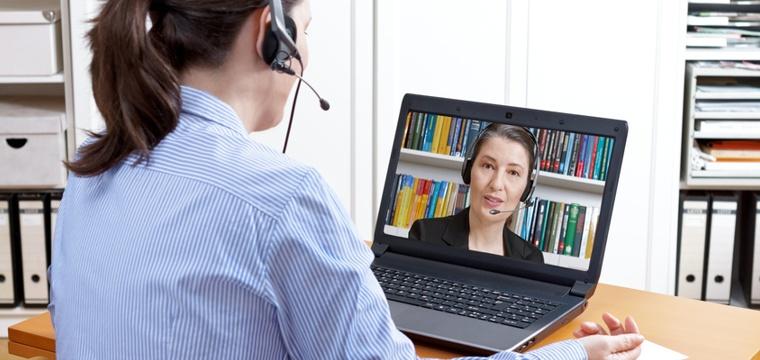 Bewerberin mit Headset vor Laptop beim Videotelefonat.