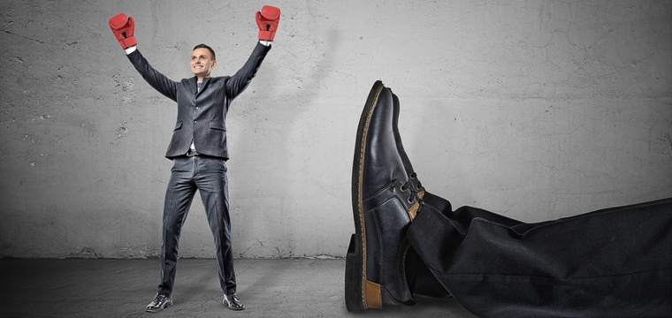 Junger Geschäftsmann mit Boxhandschuhen jubelt – er hat einen symbolischen Riesen umgehauen.