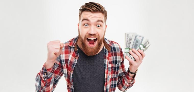 Junger Mann hält Geld in die Luft und freut sich.