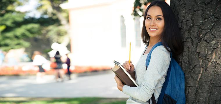 Eine junge, lächelnde Frau lehnt mit Büchern auf dem Arm an einem Baum