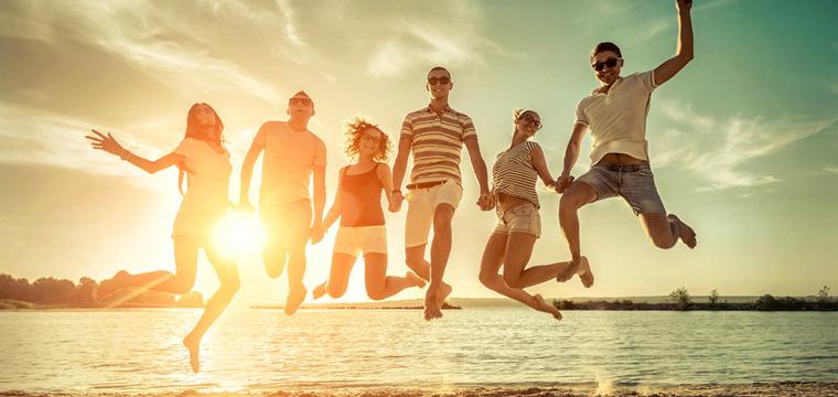 Sechs junge Menschen springen am Strand ausgelassen in die Luft.