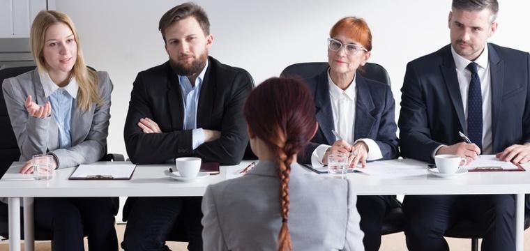 Symbolbild zur Vorbereitung aufs Vorstellungsgespräch. Eine Frau sitzt vor vier Personalern.