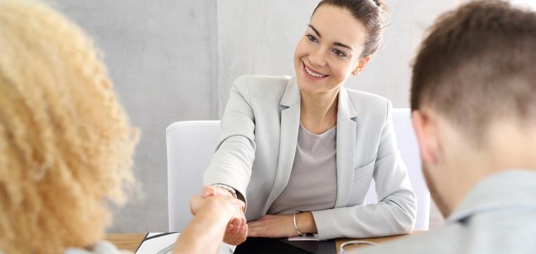 Eine Frau im Business-Outfit begrüßt zwei Personen, die ihr gegenüber sitzen.