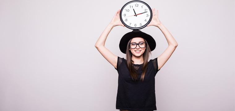 Junge Frau hält eine große Uhr über dem Kopf.