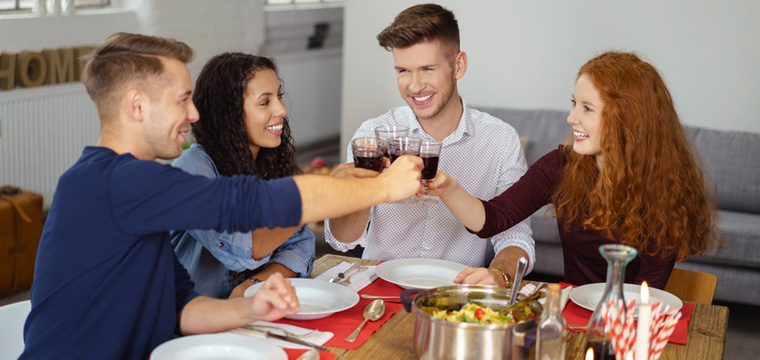Vier junge Leute sitzen am Tisch. Sie essen Pasta und trinken Wein.