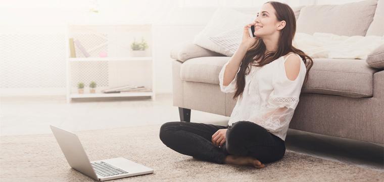Junge Frau auf Wohnzimmerboden sitzend mit Laptop und Handy.