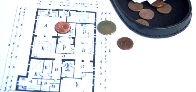 Grundriss einer Wohnung auf einem Blatt Papier. Auf dem Papier liegen eine Geldbörse und einige Geldstücke.