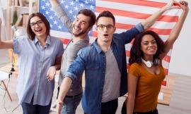 Eine Gruppe junger Studenten jubelt vor einer US-Flagge.
