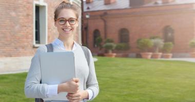 Eine junge Frau mit Laptop im Arm steht lächelnd auf dem Campus.