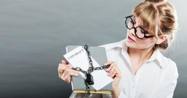 Eine junge Frau hält ein Buch und einen Vertrag, beides ist mit einer Kette und Schloss versperrt.