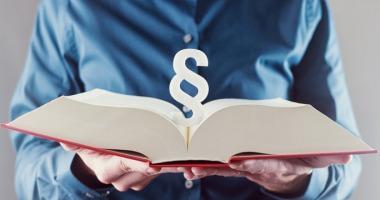Zwei Hände halten ein aufgeschlagenes Buch und ein Paragraphenzeichen.