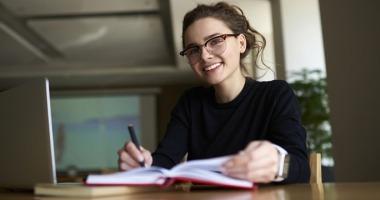 Junge Studentin arbeitet mit Computer und Notizbuch in einem Seminarraum.