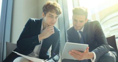 Betreuer und Student schauen sich Forschungsergebnisse auf einem Tablet an.