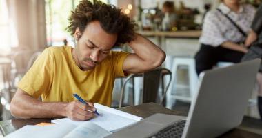 Ein Student arbeitet in einem Café an seiner Seminararbeit.