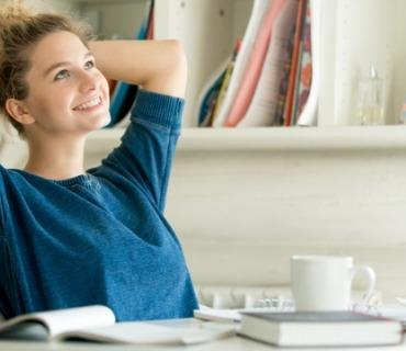 Fernstudium-Kosten – eine Frau sitzt lächelnd am Schreibtisch.