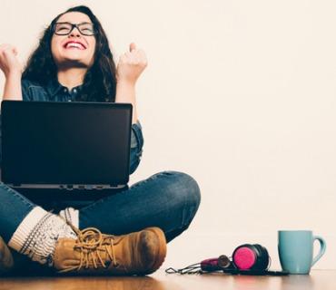 Eine junge Frau sitzt auf dem Boden. Auf ihrem Schoß befindet sich ein Laptop.