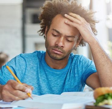 Ein junger Mann sitzt in einem Café konzentriert vor einem Buch und lernt.