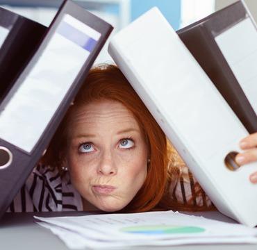 Studium neben dem Beruf: Eine Frau vergräbt ihren Kopf zwischen Aktenordnern.
