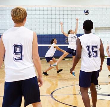 Zwei Studententeams spielen in der Turnhalle Volleyball.