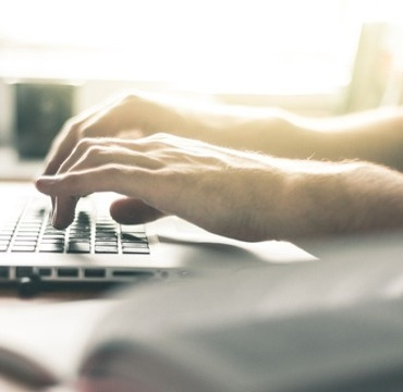 Hände tippen neben einem aufgeschlagenen Buch auf einem Laptop