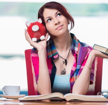 Junge Frau sitzt mit Sparschwein in der Hand zwischen Stapeln von Büchern.