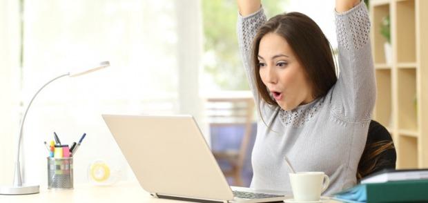 Junge Frau am Computer freut sich über gelungene Bachelorarbeit.