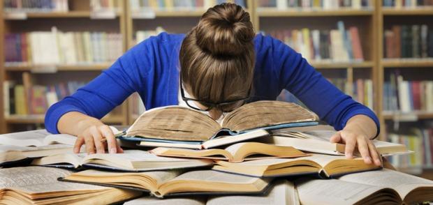 Eine junge Frau sitzt in der Bibliothek. Vor ihr ausgebreitet liegen Bücher.